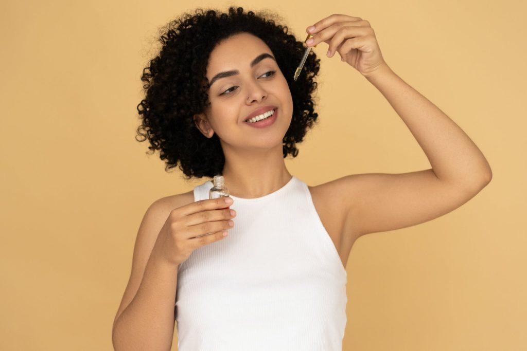 what's in my hair: girl holding hair ingredient bottle